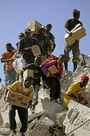 People take goods from a quake-collapsed store in Port-au-Prince, Monday, Jan. 18, 2010. (AP Photo/Ricardo Arduengo)