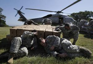 US troops with the 82nd Airborne Division take cover as a helicopter takes off after unloading relief supplies for earthquake survivors in Port-au-Prince, Haiti, Monday, Jan. 18, 2010. (AP Photo/Jae C. Hong)