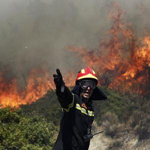 Firefighters battle to control a blaze in Palea Fokaia, south of Athens (AP)