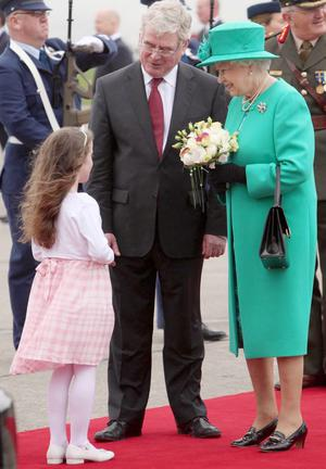 Queen Elizabeth II holds a posy of flowers given to her by eight-year-old Rachel Fox after she was greeted by Tanaiste Eamon Gilmore upon arrival at Casement Aerodrome, Baldonnel