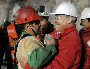 In this photo released by the Chilean presidential press office, Chile's President Sebastian Pinera, right, hugs rescued miner Mario Sepulveda after Sepulveda was rescued from the collapsed San Jose gold and copper mine where he was trapped with 32 other miners for over two months near Copiapo, Chile, early Wednesday Oct. 13, 2010.  (AP Photo/Jose Manuel de la Maza, Chilean presidential press office)