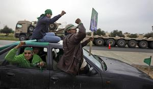 Pro-Gadhafi supporters in a car speed past a vehicle used to transport tanks from the Libyan military's elite Khamis Brigade, led by Gadhafi's youngest son Khamis Gadhafi, hours after the Khamis units were deployed on the road in Harshan, 10km east of Zawiya, in Libya, Monday, Feb. 28, 2011. Rebel forces in Zawiya were locked in a standoff with Gadhafi loyalists and residents inside the city said they were anticipating a possible attack. (AP Photo/Ben Curtis)