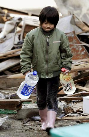 Boy carries bottles of water amid debris in Kesennuma, northern Japan Monday, March 14, 2011 following Friday's massive earthquake and the ensuing tsunami. (AP Photo/Kyodo News) JAPAN OUT, MANDATORY CREDIT, NO SALES IN CHINA, HONG  KONG, JAPAN, SOUTH KOREA AND FRANCE, CORRECTS DATE PHOTO TAKEN