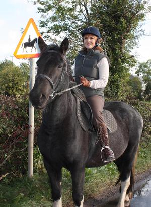 Back in the saddle: Iris Robinson MP MLA by a hazard sign in Comber to alert drivers to horses and riders. All too often these signs are being ignored, putting lives in danger, says Mrs Robinson. She has called for improved facilities for horses and riders on local roads