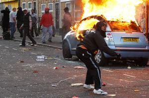 LONDON, ENGLAND - AUGUST 08:  A rioter throws a rock at riot police in Clarence Road in Hackney on August 8, 2011 in London, England. Pockets of rioting and looting continues to take place in various boroughs of London this evening, as well as in Birmingham, prompted by the initial rioting in Tottenham and then in Brixton on Sunday night. It has been announced that the Prime Minister David Cameron and his family are due to return home from their summer holiday in Tuscany, Italy to respond to the rioting. Disturbances broke out late on Saturday night in Tottenham and the surrounding area after the killing of Mark Duggan, 29 and a father-of-four, by armed police in an attempted arrest on August 4.  (Photo by Dan Istitene/Getty Images)