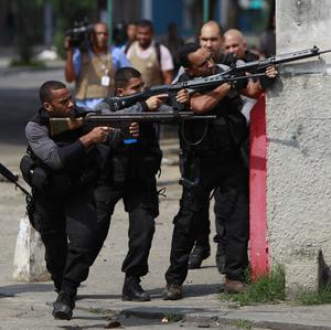 Police officers in Rio aim their weapons during an operation against drug traffickers (AP)