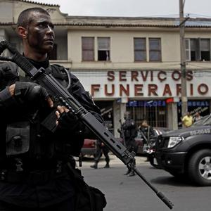 A police officer stands guard in front of a funeral house during an operation at the Vila Cruzeiro slum in Rio de Janeiro (AP)