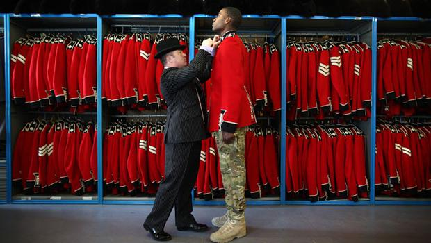 WINDSOR, ENGLAND - APRIL 21:  Irish Guardsman Bortnill St'Ange is fitted with his ceremonial uniform by Master Tailor Lance Sergeant Matthew Else in the store room at Victoria Barracks on April 21, 2011 in Windsor, England. The Irish Guards returned from active duty in Afghanistan at the beginning of April, and are now preparing for ceremonial duties. Prince William is the Colonel of the Regiment and the Irish Guards will be on duty at the Royal Wedding on April 29, 2011.  (Photo by Peter Macdiarmid/Getty Images) *** Local Caption *** Bortnill St'Ange;Matthew Else;