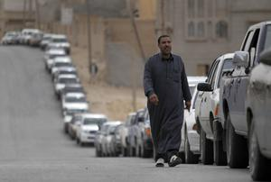 A Libyan man walks as drivers wait in line in their cars for gasoline at a gas station that was just reopened after many days closed because of the fighting between Government and anti-government forces in the southwester town of Nalut, Libya,  Monday, Feb. 28, 2011. The town is currently in control of the Libyan anti-government forces. (AP Photo/Lefteris Pitarakis)