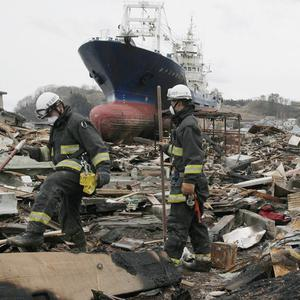 A search and rescue team moves through the rubble in the devastated city of Kesennuma, with a stranded ship behind them (AP)