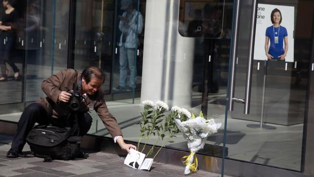 A Chinese photographer adjusts a picture of Steve Jobs near flowers laid in tribute outside an Apple retail store in Beijing, China, Thursday, Oct. 6, 2011.  Steve Jobs, the co-founder of Apple Inc. and father of the iPhone, has died at age 56. (AP Photo/Ng Han Guan)
