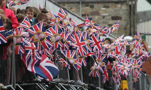 Crowds wait in heavy rain in Enniskillen, County Fermanagh, for the arrival of Queen Elizabeth II during a two-day as part of the Diamond Jubilee tour