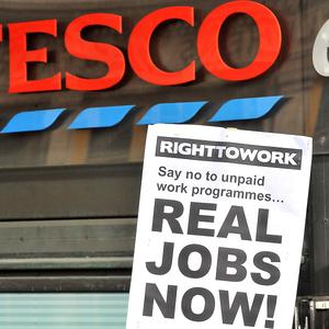A Right to Work campaigner holds a banner outside the Tesco Express store at Portcullis House, Westminster