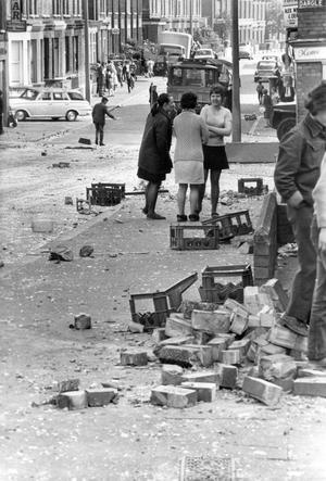After their night of terror the residents of Belfast's Manor Street clear up the glass, bricks and debris.  12/6/1972