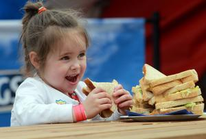 Lucy Reel, aged 4, from Newry is pictured enjoying a Kingsmill Sandwich at Balmoral Show. The Kingsmill 'Mum Break', housed in a giant inflatable loaf, is offering mums a handy pit stop during Ireland's largest agricultural and food show.