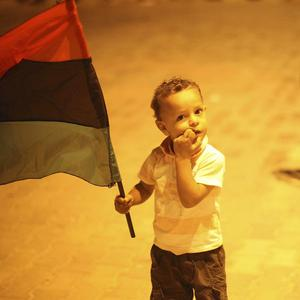 Mustafa Saad, five, holds a flag during celebrations in Tripoli (AP)