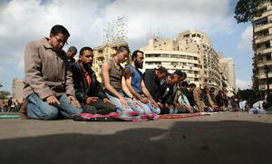 CAIRO, EGYPT - JANUARY 30:  People pray in Tahrir Square on January 30, 2011 in Cairo, Egypt. As President Mubarak struggles to regain control after five days of protests he has appointed Omar Suleiman as vice-president. The present death toll stands at 100 and up to 2,000 people are thought to have been injured during the clashes which started last Tuesday. Overnight it was reported that thousands of inmates from the Wadi Naturn prison had escaped and that Egyptians were forming vigilante groups in order to protect their homes after Police were nowhere to be seen on the streets. Broadcasts from the Al-Jazeera television network via an Egyptian satellite have now been halted.  (Photo by Peter Macdiarmid/Getty Images)