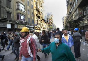 Egyptian protesters run from the scene of a building fire, seen in background, near Tahrir Square in Cairo, Egypt, Monday, Nov. 21, 2011.  local people at the scene blame the fire on police firing tear gas in the area.  Egyptian riot police clashed Monday with thousands of protesters demanding that the ruling military quickly announce a date to hand over power to an elected government.  (AP Photo/Amr Nabil)
