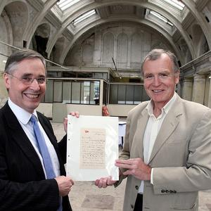 Dr John Martin, right, receives a letter sent from the Titanic, from Bryan Gregory, acting chief executive of the Titanic Foundation