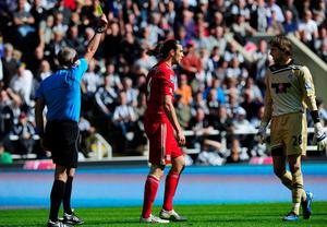 NEWCASTLE UPON TYNE, ENGLAND - APRIL 01:  Liverpool striker Andy Carroll is booked by referee Martin Atkinson during the Barclays Premier League match between Newcastle United and Liverpool at Sports Direct Arena on April 1, 2012 in Newcastle upon Tyne, England.  (Photo by Stu Forster/Getty Images)