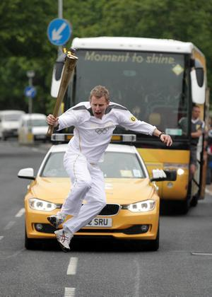 Patrick Kielty carrying the Olympic Flame on the Torch Relay leg between Newcastle and Downpatrick