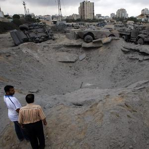Palestinians check the damage caused by an Israeli air strike in Ansar security compound used by Gaza's Islamic militant Hamas. (AP)