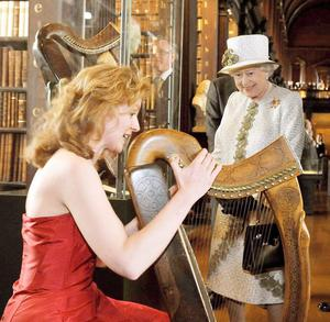 Britain's Queen Elizabeth II  listens to the story of the traditional Irish Harp, from Harpist Siobhan Armstrong who was playing during a tour at Trinity College in Dublin, this afternoon.  PRESS ASSOCIATION Photo.