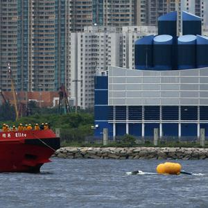 A fireboat approaches a crashed helicopter, right, in Hong Kong Victoria Harbour. (AP)