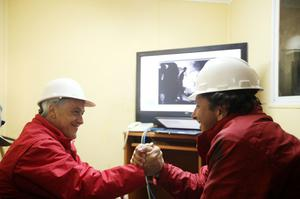 SAN JOSE MINE, CHILE - OCTOBER 12: (NO SALES, NO ARCHIVE) In this handout from the Chilean government, Chilean President Sebastian Pinera (L) and Mining Minister Laurence Golborne shake hands after Roberto Rios, a technical expert arrived at the bottom of the rescue hole October 12, 2010 at the San Jose mine near Copiapo, Chile. The rescue operation has begun bringing up the 33 miners, 69 days after the August 5th collapse that trapped them half a mile underground. (Photo by Hugo Infante/Chilean Government via Getty Images)