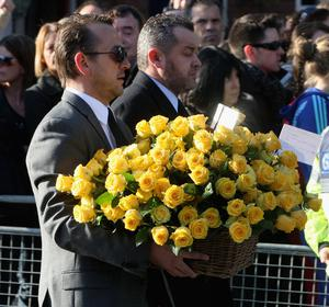 Men carry flowers given by Elton John to the funeral of Boyzone singer Stephen Gately at St Laurence O'Toole Church in Dublin