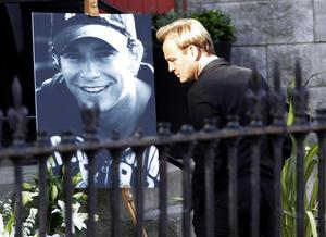 Jason Donovan looks at a tribute as he arrives at St Laurence O'Toole Church in Dublin for the funeral of Stephen Gately