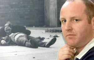 Paul Doherty in front of an image of his dying father Patrick Doherty who was shot on Bloody Sunday.