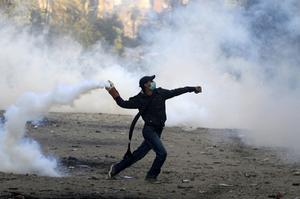A protester throws a tear gas cannister during clashes with Egyptian riot police near Tahrir Square in Cairo, Egypt, Monday, Nov. 21, 2011. Security forces fired tear gas and clashed Monday with several thousand protesters in Cairo's Tahrir Square in the third straight day of violence that has killed at least two dozen people and has turned into the most sustained challenge yet to the rule of Egypt's military.(AP Photo/Khalil Hamra)
