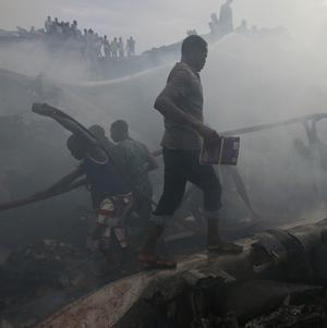 Rescue workers search for bodies after a plane crash in Lagos, Nigeria (AP)