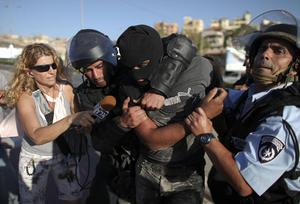 Israeli police detain a masked Arab Israeli protester, center, as an Israeli journalist tries to interview him, during clashes in the northern Arab Israeli town of Umm el-Fahm, Monday, May 31, 2010
