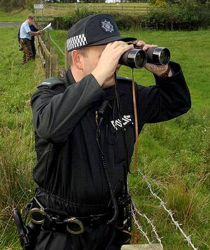 A policeman looks for evidence following recent sightings in Co Down