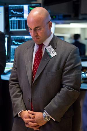 NEW YORK, NY - DECEMBER 17:  A trader on the floor of the New York Stock Exchange holds a moment of silence in honor of those killed in the shooting massacre in Newtown, CT, on December 17, 2012 in New York City. Twenty children and seven adults were killed by a 20-year-old Adam Lanza on December 14, 2012.  (Photo by Andrew Burton/Getty Images)