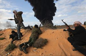 RAS LANUF, LIBYA - MARCH 09:  Libyan rebels take cover from government fire as a natural gas facility burns on the frontline on March 9, 2011 near Ras Lanuf, Libya. The rebels pushed back government troops loyal to Libyan leader Muammar Gaddafi towards Ben Jawat.  (Photo by John Moore/Getty Images)
