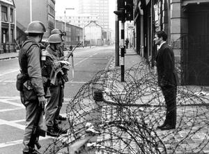 A man talks to soldiers over the barricade, in Divis Street, Belfast. 16/8/1969