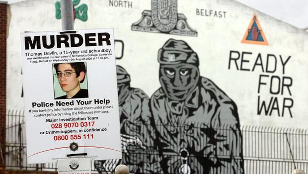 A Thomas Devlin murder appeal poster beside a UVF (Ulster Volunteer Force) mural in the Mount Vernon area of North Belfast opposite the flats where one of his killers had lived.