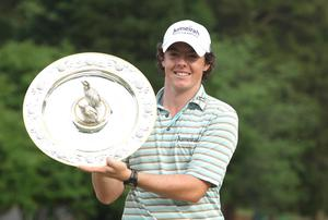 Rory McIlroy poses with the winner's trophy after his four-stroke victory at the 2010 Quail Hollow Championship yesterday