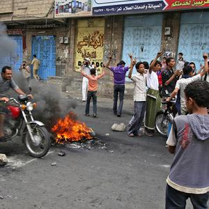 Anti-government protestors block the road with rocks and burning tires during clashes with Yemeni security forces in Taiz, Yemen