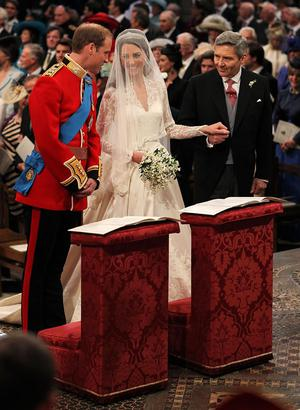 LONDON, ENGLAND - APRIL 29: Prince William speaks to his bride, Catherine Middleton as she holds the hand of her father Michael Middleton on April 29, 2011 in London, England.  The marriage of Prince William, the second in line to the British throne, to Catherine Middleton is being held in London today. The marriage of the second in line to the British throne is to be led by the Archbishop of Canterbury and will be attended by 1900 guests, including foreign Royal family members and heads of state. Thousands of well-wishers from around the world have also flocked to London to witness the spectacle and pageantry of the Royal Wedding.  (Photo by Dominic Lipinski - WPA Pool/Getty Images)