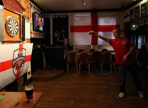 A England soccer supporter is seen playing darts after they have watched the Euro 2012 soccer championship Group D match between France and England, at a pub called The Clock, in Hebburn, England, Monday, June 11, 2012