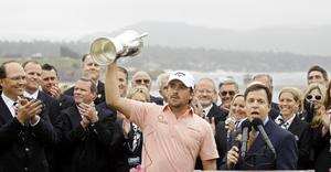 Graeme McDowell of Northern Ireland celebrates with the trophy on the 18th green after winning the 110th U.S. Open at Pebble Beach Golf Links on June 20, 2010 in Pebble Beach, California