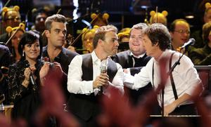 From left, Lily Allen, Robbie Williams and Take That's Gary Barlow, James Corden and Sir Paul McCartney, on stage at the BBC Children in Need Rocks concert