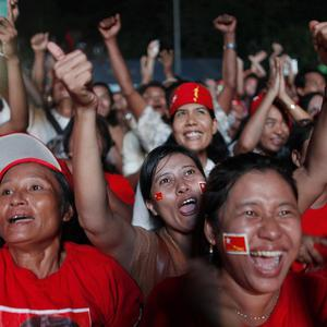 Aung San Suu Kyi's supporters cheer after the party's announcement outside the party headquarters. (AP)