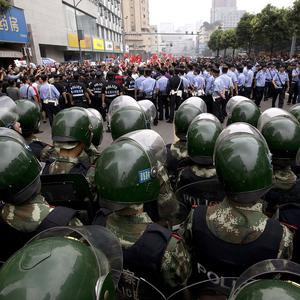 A group of demonstrators is surrounded by uniformed policemen and paramilitary policemen during a protest against Japan in Chengdu (AP)