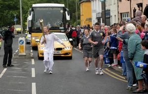 Patrick Kielty kisses the torch as he carries the Olympic Flame on the Torch Relay leg between Newcastle and Downpatrick