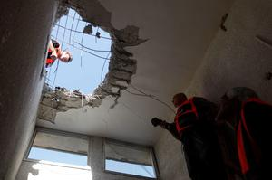 ASHKELON, ISRAEL- NOVEMBER 18:  (ISRAEL OUT) Israeli workers inspect the damage to a house that was hit by a rocket fired by Palestinian militants from the Gaza Strip on November 18, 2012 in Ashkelon, Israel.  Israeli/Gaza attacks have entered the fifth day, with two media buildings being recently struck and several journalists subsequently injured. According to health officials in Gaza, at least 50 Palestinians have been killed since Israel launched operation Pillar of Defence. So far three Israelis have died in the exchange of missiles which followed an air strike on Wednesday that killed Hamas military chief Ahmed Jabari. (Photo by Lior Mizrahi/Getty Images)